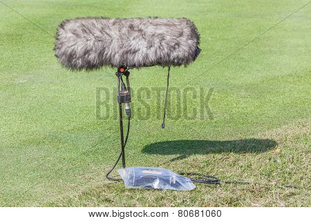 Close-up The Professional Sport Microphone And Set Situated On The Green Grass.