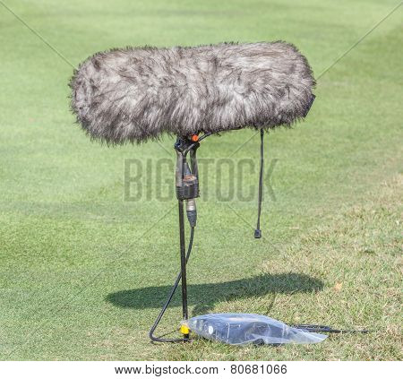 A Large Microphone Boom With Windshield Situated At The Ground.