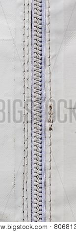 Close Up White Zipper And Rough Stitching On White Canvas Tent.