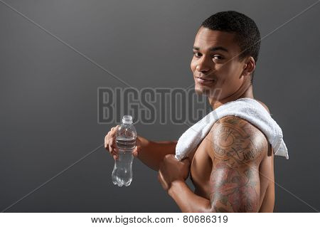 Young Africana sportsman drinking water after workout