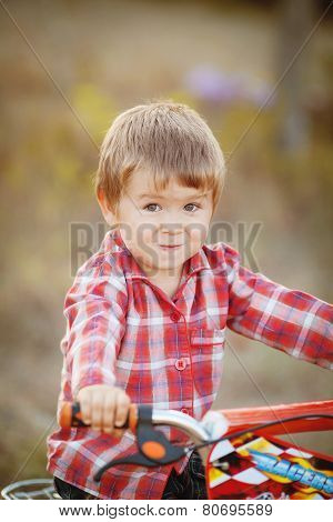Little boy riding in the Park by bike.
