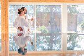 foto of infinity pool  - Couple on pool looking relaxed throw window of wellness spa wearing bath robe - JPG