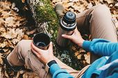 foto of thermos  - Unrecognizable traveler woman holding a cup of tea or coffee and thermos in autumn forest - JPG