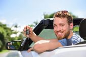picture of road trip  - Man driving rental car showing new car keys happy - JPG