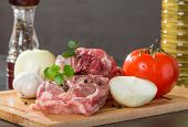 stock photo of lamb chops  - raw lamb leg chops on a wooden chopping board with garlic onion pepper tomato and vegetable oil - JPG