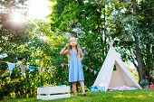 pic of tipi  - Adorable little girl having fun playing outdoors on summer day - JPG