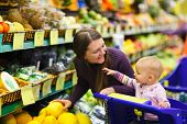 stock photo of supermarket  - Mother and baby daughter in supermarket buying fruits and vegetables - JPG