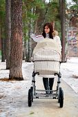 image of buggy  - reading book young mother with baby buggy  - JPG