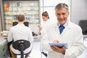 picture of hospital  - Senior pharmacist using tablet pc at the hospital pharmacy - JPG