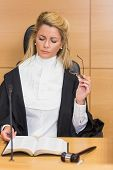 picture of court room  - Stern judge reading her notes in the court room - JPG