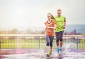 foto of rainy weather  - Young couple jogging on asphalt in rainy weather - JPG