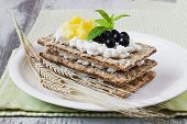 stock photo of mountain-ash  - rye bread with cottage cheese black berries of mountain ash and mango on a white wooden background - JPG
