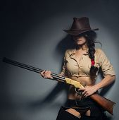 foto of guns  - girl cowboy with a gun on a gray background - JPG