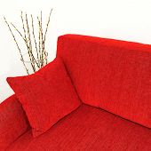 stock photo of futon  - Red velvet sofa with cushion and willow branches in a vase - JPG
