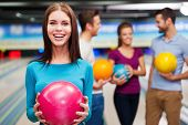 stock photo of bowling ball  - Beautiful young women holding a bowling ball while three people communicating against bowling alleys - JPG