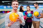 stock photo of bowling ball  - Handsome young men holding a bowling ball while three people communicating against bowling alleys - JPG