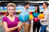 foto of bowling ball  - Beautiful young women holding a bowling ball while three people communicating against bowling alleys - JPG
