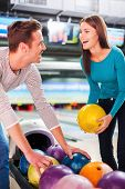 pic of bowling ball  - Cheerful young couple looking at each other and choosing bowling balls while standing against bowling alleys - JPG