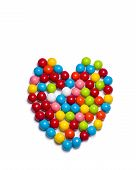 stock photo of gumballs  - Multicolored gumballs arranged in a heart shaped configuration lying on a white background - JPG