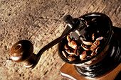 foto of wooden box from coffee mill  - Fragment grinder with roasted coffee beans on a wooden background - JPG