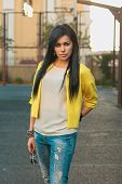stock photo of swagger  - Beautiful girl in a yellow jacket and jeans holds glasses