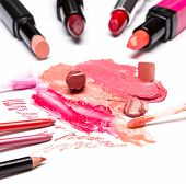 picture of  lips  - Different colors of smeared and sliced lipstick lip gloss with brushes lip liner on white textured surface - JPG