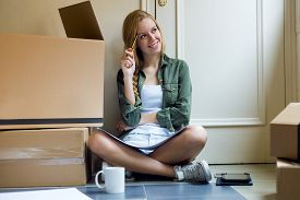 pic of independent woman  - Portrait of young beautiful woman moving in new home - JPG