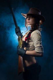 stock photo of girls guns  - girl cowboy with a gun on a gray background - JPG