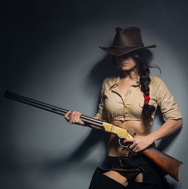 picture of girls guns  - girl cowboy with a gun on a gray background - JPG