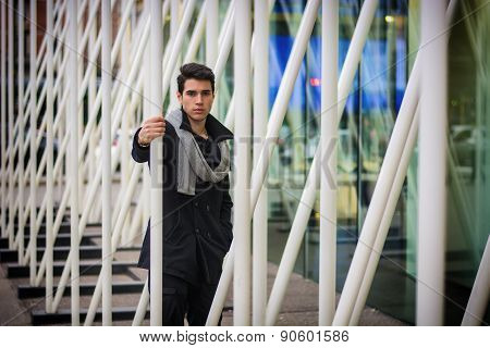Young Handsome Man among White Metal Bars