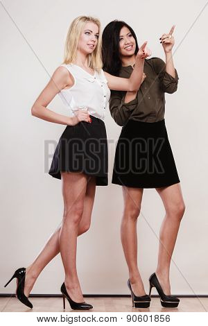 Two Fashion Women Pointing Wit Finger