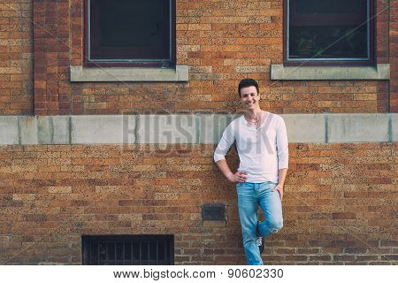 Stylish Casual Sexy And Happy Man Lean Back Brick Building.