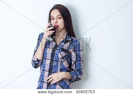 Young woman posing at camera and drinking red wine