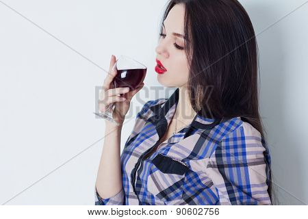 Girl languidly looks at glass of red wine
