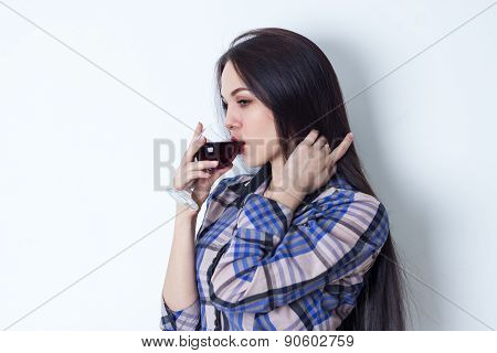 Young woman stroking her hair and drinking red wine