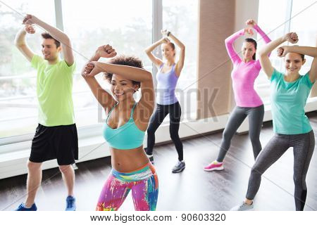 fitness, sport, dance and lifestyle concept - group of smiling people with coach dancing zumba in gym or studio