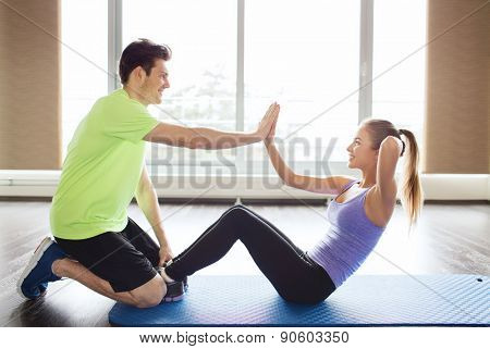 fitness, sport, training, teamwork and people concept - happy woman with personal trainer doing sit ups and high five gesture in gym