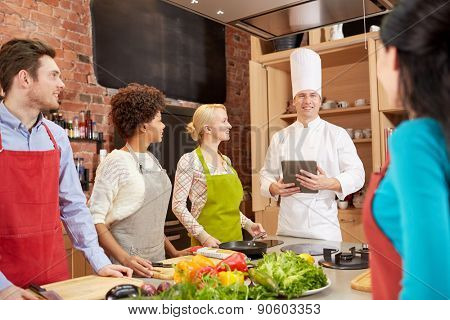 cooking class, culinary, food, technology and people concept - happy friends with tablet pc in kitchen