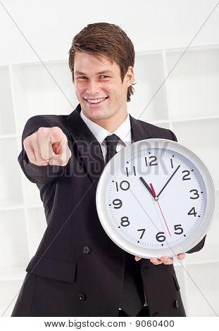confident businessman holding clock