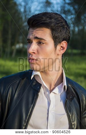 Handsome young man at countryside, with strange, unsure expression