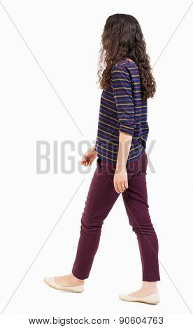 back view of walking  woman.  backside view of person.  Rear view people collection. Isolated over white background. Curly girl in red jeans and a striped sweater