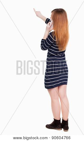 back view of pointing young beautiful  woman and using a mobile phone. girl  watching. Rear view people collection.  backside view of person.  Isolated over white background.