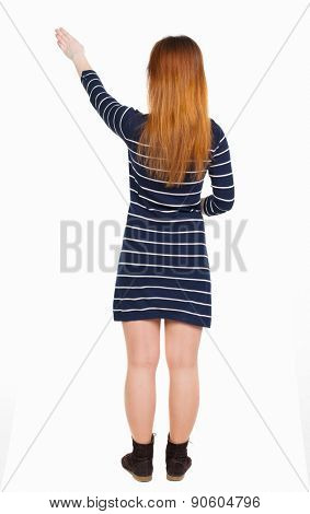back view of woman. Young woman in vest presses down on something. Isolated over white background. Rear view people collection.  she holds his hand open, palm forward. The guide shows the exhibits.