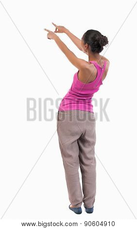 back view of woman. Young woman in vest presses down on something. Isolated over white background. Rear view people collection. backside view of person. African-American woman shows her hands in right