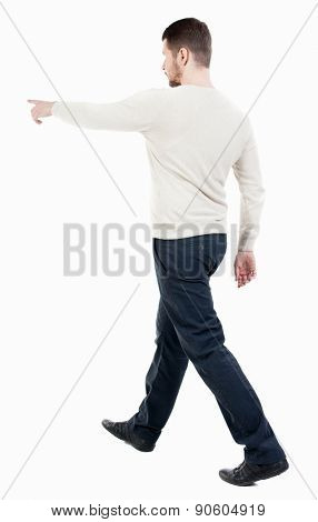 Back view of going handsome man in jeans pointing. walking young guy . Rear view people collection.  backside view of person.  Isolated over white background. Man approaching object shows up on him.