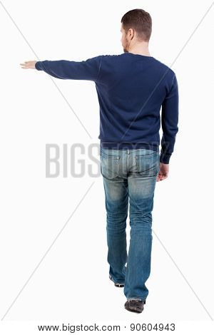 Back view of going  handsome man in jeans pointing. walking young guy . Rear view people collection.  backside view of person.  Isolated over white background. guy in jeans goes to right showing left