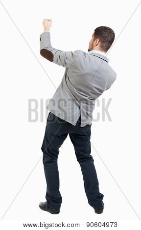 back view of standing man pulling a rope from top or cling to something.  Rear view people collection.  Isolated over white background. Businessman pulling a rope on top of something.