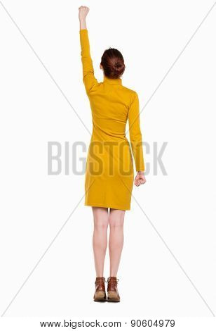 Back view woman. Raised his fist up in victory sign. Rear view people collection.  backside view of person. Isolated over white background. Girl in a mustard-colored dress standing in pose superhero