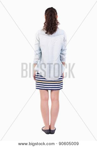 back view of standing young beautiful  woman. girl  watching. Rear view people collection.  backside view of person. Isolated over white background. curly girl in striped skirt stands with her hands.