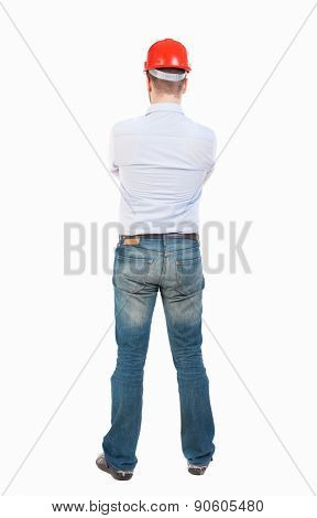 Backview of an engineer in construction helmet stands. Standing young guy. Rear view people collection.  backside view of person. Isolated over white background. Engineer crossed his arms and watches.